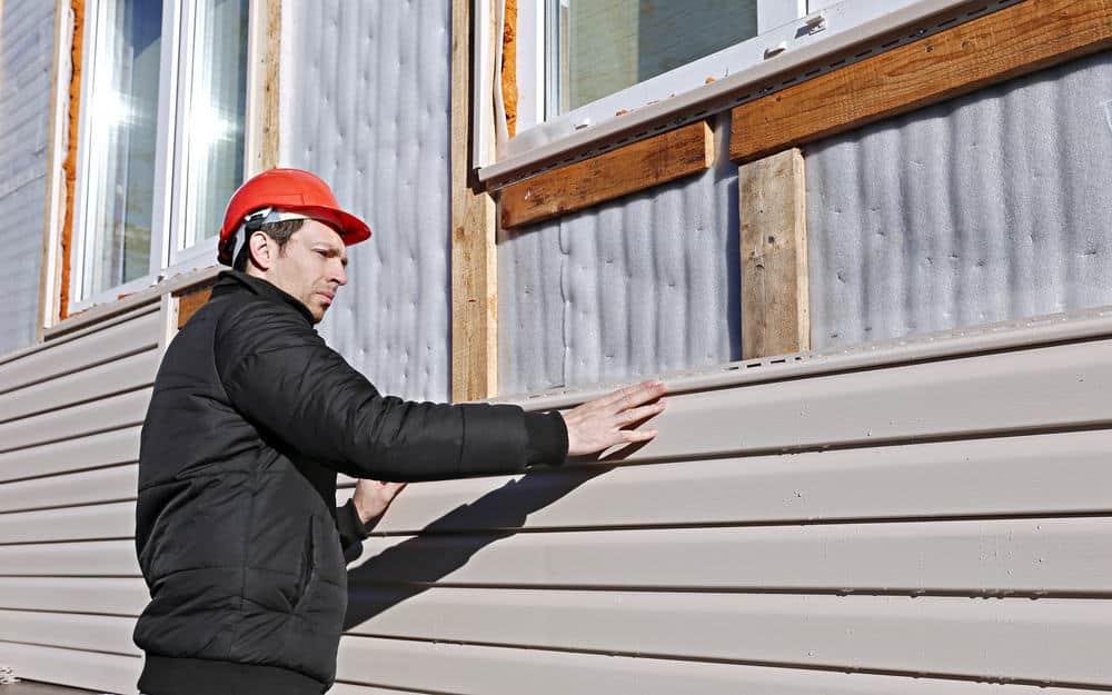 Un ouvrier installe beige panneaux bardage sur la façade